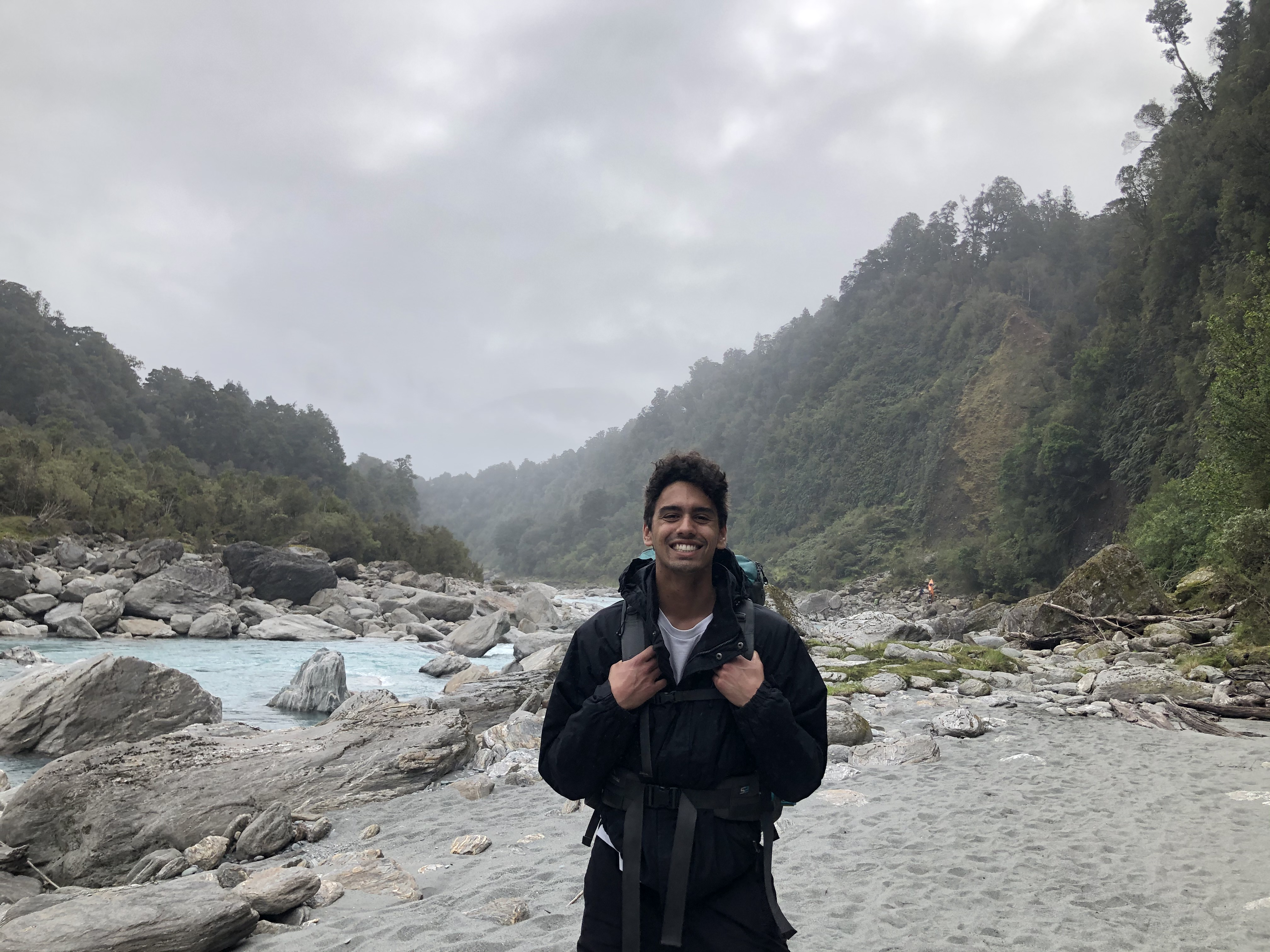 Young man standing and smiling at the camera whilst gripping the straps of his backpack which is on his shoulders. Behind him is a blue river, a rocky river bed and pine trees. There is a grey cloudy sky with mist starting to cover the trees.