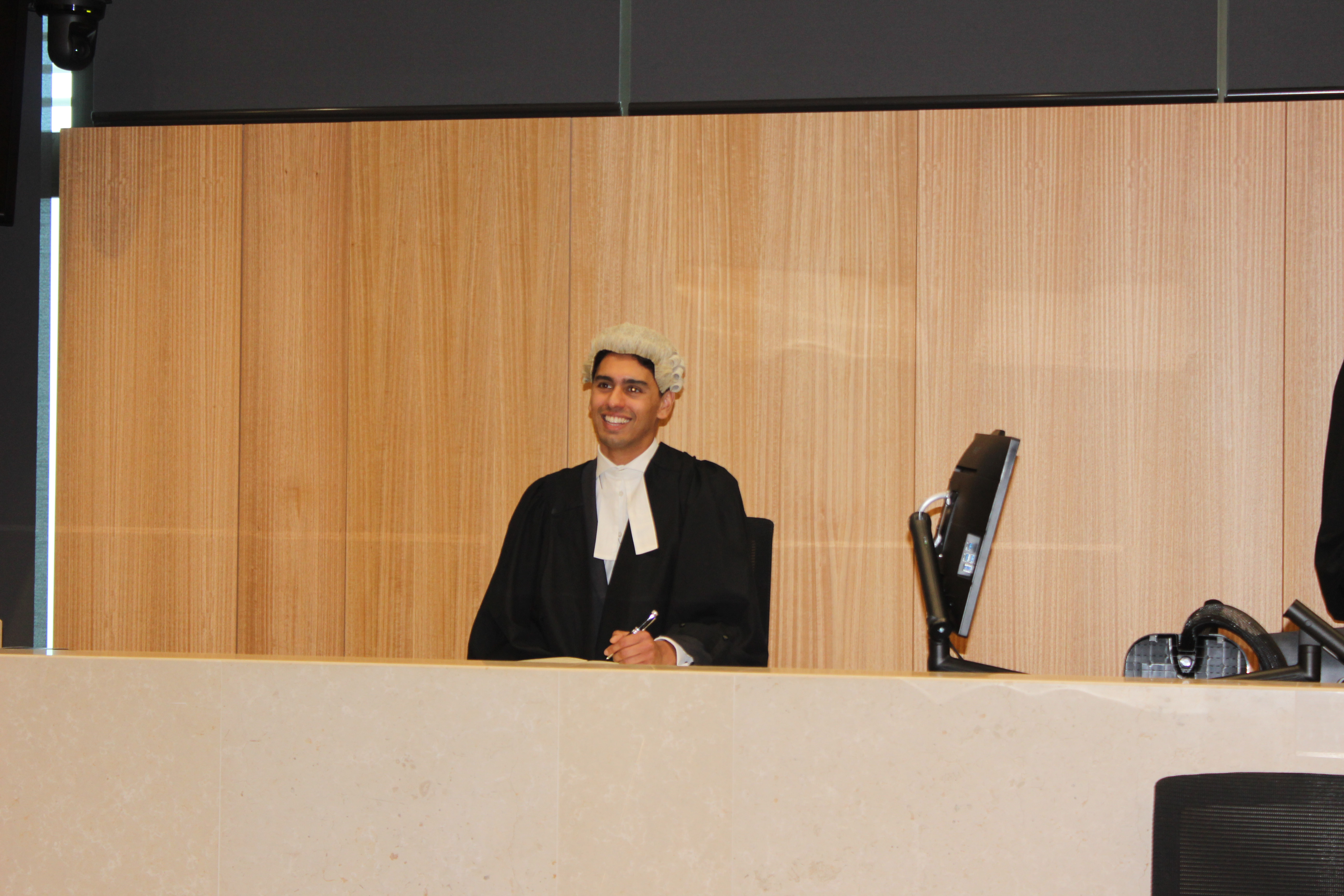 Ravi sits in the court room wearing a black gown and a while curly wig. He is smiling.