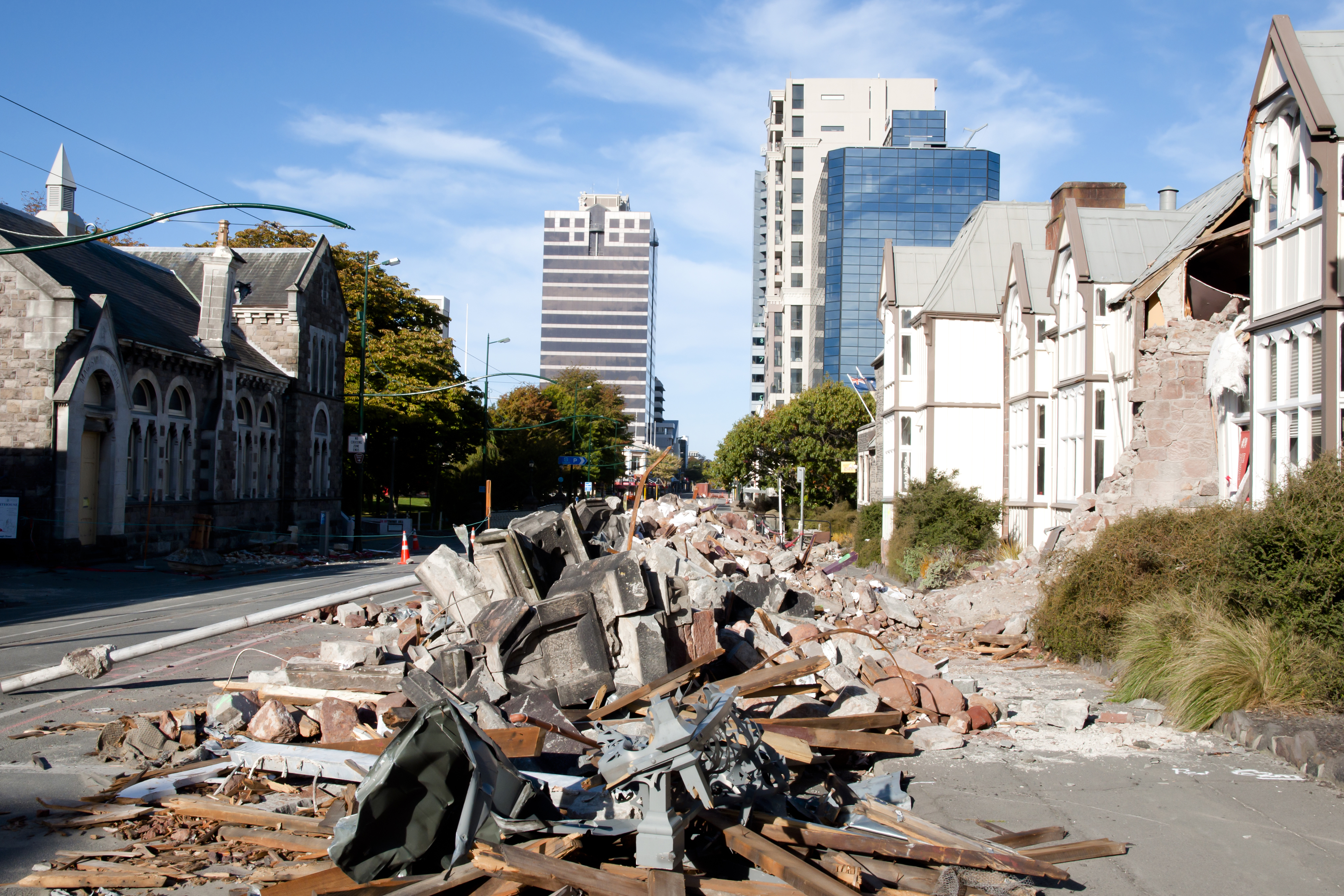 Pile of rubble in the street, houses with the front falling down due to earthquake. Office towers in the background.